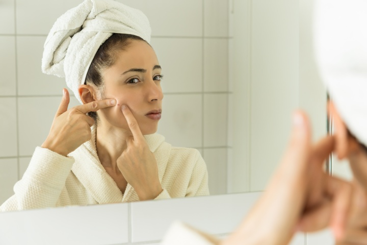 Woman wearing a bathrobe looking to mirror and squeezing a pimple